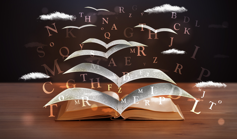 Pages and glowing letters flying out of a book on wooden deck